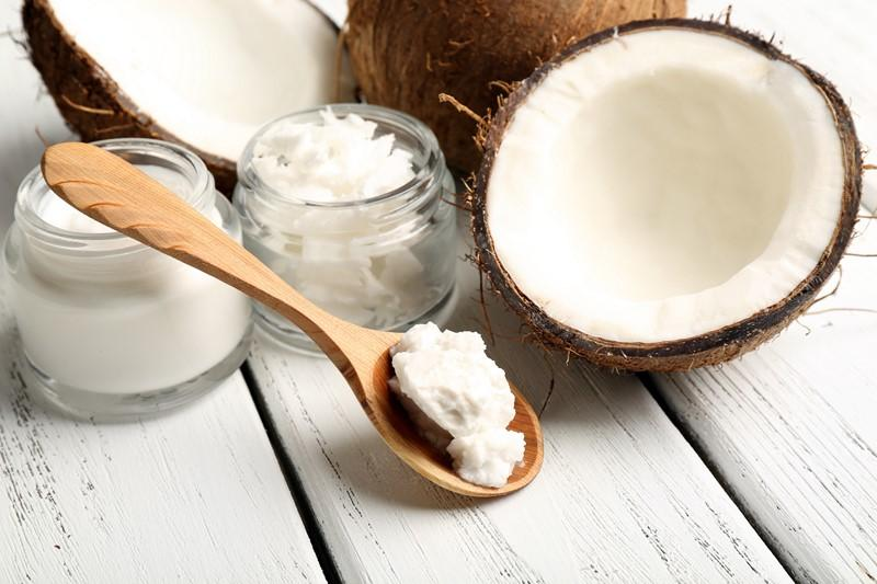 coconut-with-jars-of-coconut-oil-and-cosmetic-cream-on-wooden-background