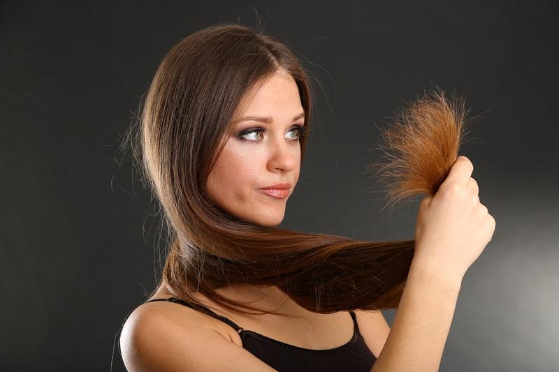 beautiful-woman-holding-split-ends-of-her-long-hair-on-black-background