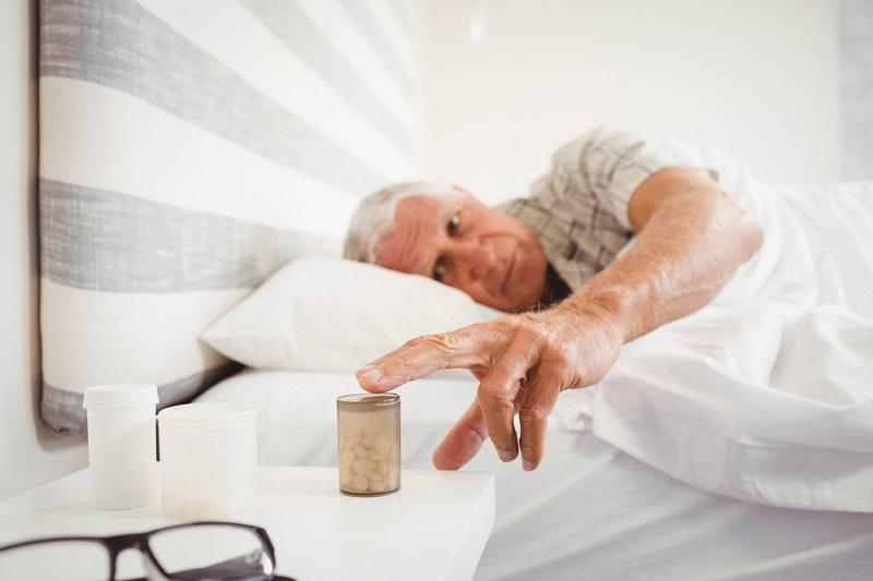 senior-man-picking-up-pill-bottle-while-sleeping-in-bedroom