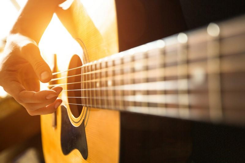 female-hand-close-up-playing-on-acoustic-guitar
