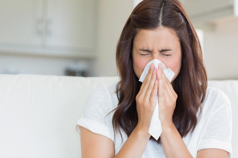 brunette-sneezing-in-a-tissue-in-the-living-room